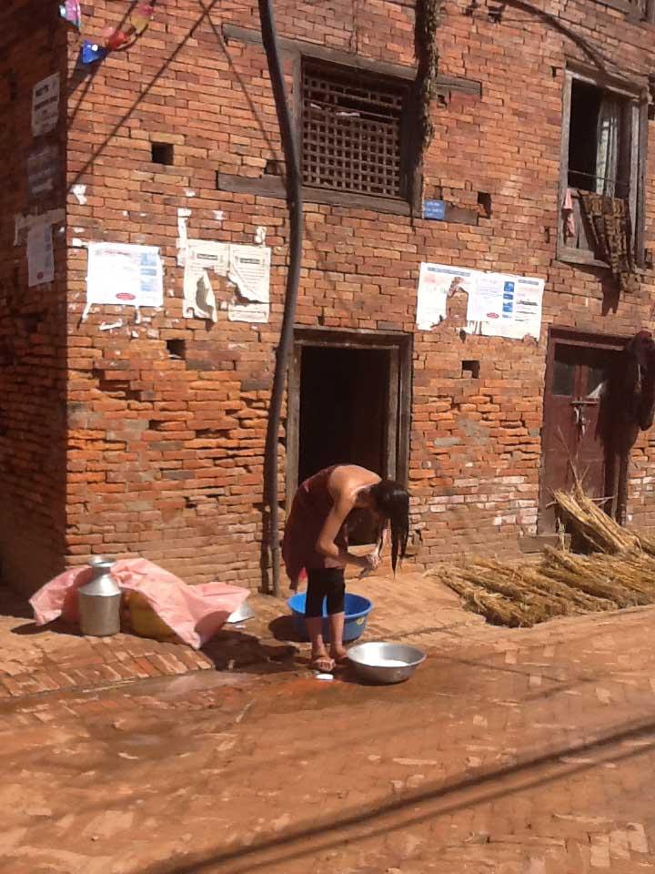 Banho de uma moça nepalesa na zona rural,e mais rústica, de Katmandu